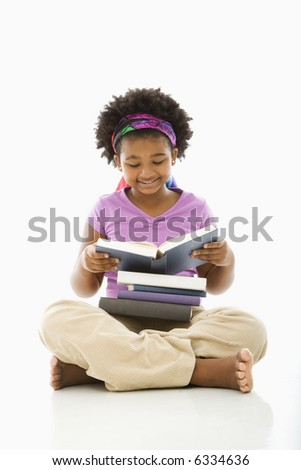 African American girl with large stack of books reading. - stock photo