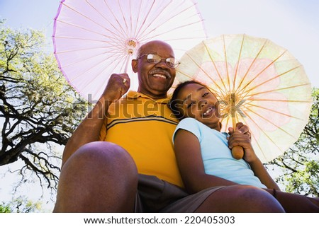 African American grandfather and granddaughter with parasols - stock photo