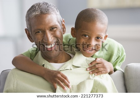African American grandfather and grandson hugging - stock photo
