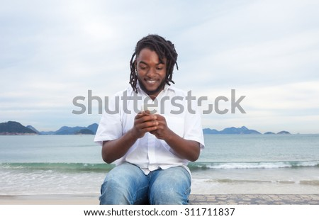 African american guy with dreadlocks and white shirt typing message - stock photo