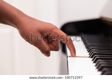 African American hand playing piano  - Touching piano keys - Black people - stock photo