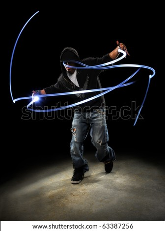 African American hip hop dancer with LED lights painting patterns - stock photo