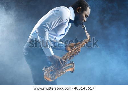 African American jazz musician playing the saxophone against colorful smoky background - stock photo