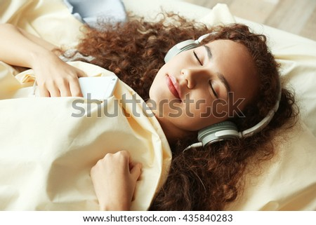 African American listening to music in headphones in bed - stock photo