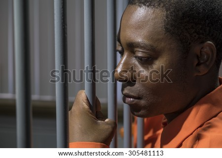 African American male behind bars in a jail cell - stock photo