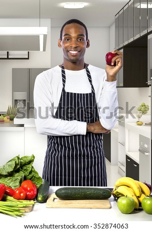 African American male chef wearing an apron in a home or restaurant kitchen.  He is preparing a healthy meal. - stock photo