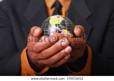 African-American male hands cradling a globe. - stock photo