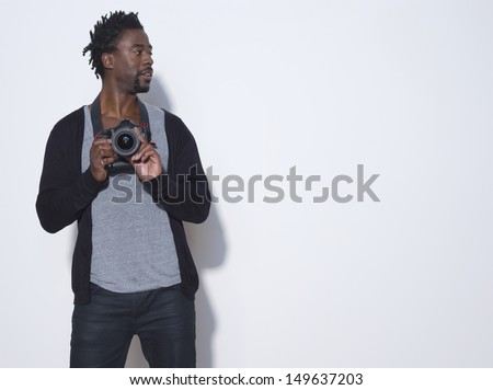 African American male photographer camera looking away in studio - stock photo