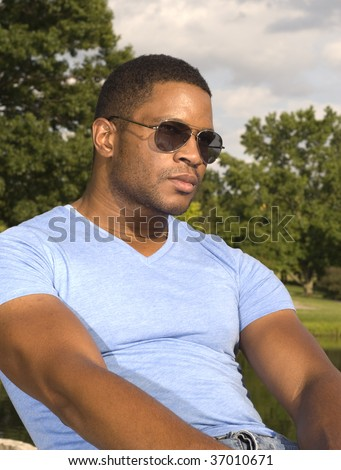 African American Male with Sunglasses leaning back - stock photo