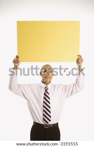 African American man holding blank yellow sign overhead standing against white background. - stock photo