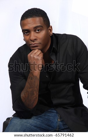 African American man posing with hand on his chin.  In thinking position - stock photo