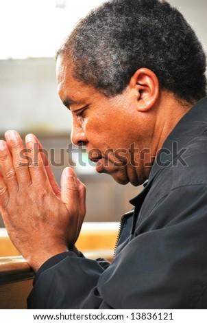 African american man praying in church. - stock photo