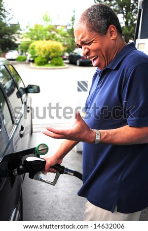 African american man pumping high price gasoline into his car. - stock photo