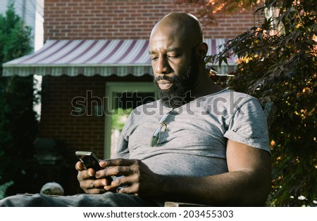 African American man reacts as he reads and email or text message while enjoying a glass for red wine in the backyard garden - stock photo