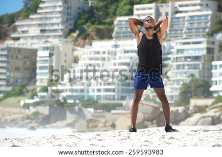 African american man relaxing after work out at the beach  - stock photo