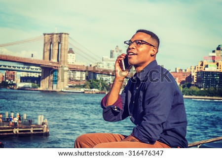 African American Man traveling in New York. Wearing blue shirt, brown pants, glasses, a college student sitting by East River, looking at sky, smiling, talking on phone. Brooklyn bridge on background. - stock photo