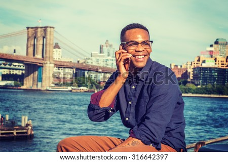 African American Man traveling in New York. Wearing blue shirt, brown pants, glasses, a college student sitting by East River, looking around, smiling, talking on phone. Brooklyn bridge on background. - stock photo