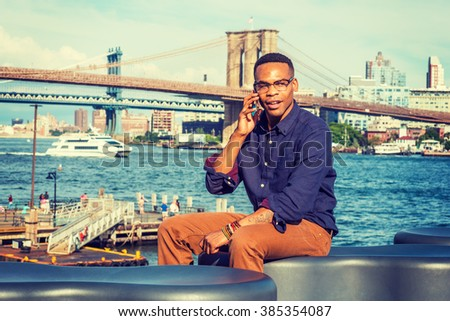 African American Man traveling, working in New York. Wearing blue shirt, brown pants, glasses, a college student sitting by river, talking on phone. Boat, Manhattan, Brooklyn bridges on background.  - stock photo