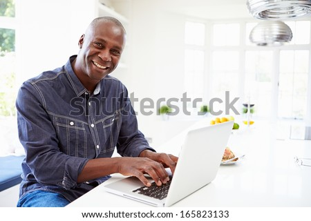 African American Man Using Laptop At Home - stock photo