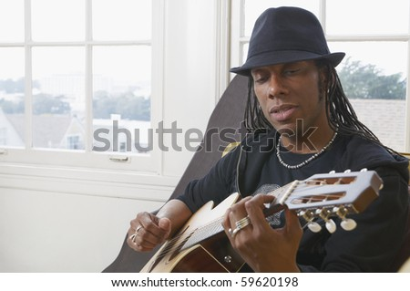 African American man wearing a hat and playing acoustic guitar - stock photo