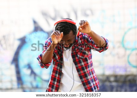 African American man with headphones outdoors - stock photo