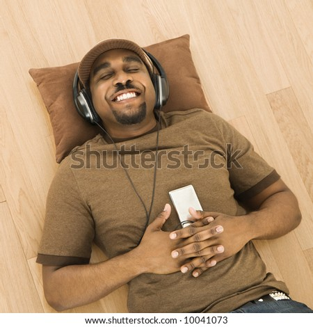 African-American mid-adult man wearing headphones and listening to mp3 player while lying on back on floor. - stock photo