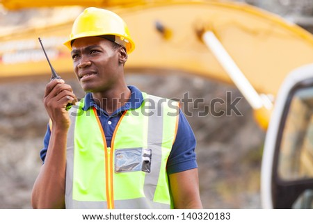 african american mine worker with walkie-talkie at mining site - stock photo