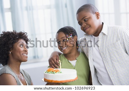 African American mother and children with birthday cake - stock photo