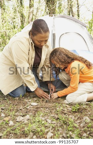 African American mother and daughter setting up tent - stock photo