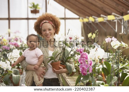 African American mother with baby in greenhouse - stock photo