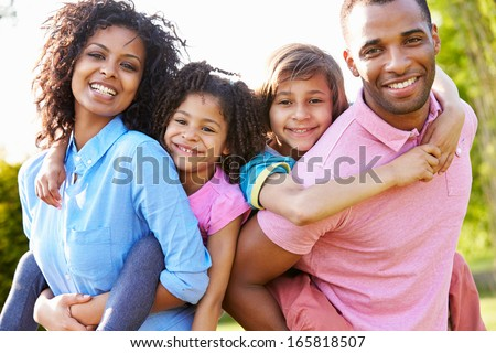 African American Parents Giving Children Piggyback Rides - stock photo