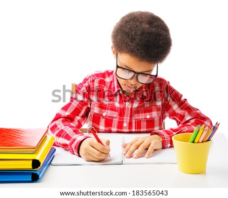 African American school boy focused doing homework, exam, taking test. Concept of education. Isolated, over white background, with copy space - stock photo