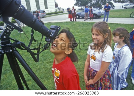 African American school girl looking through telescope at Solar Eclipse with friends waiting in line, Griffith Observatory, Los Angeles, CA - stock photo
