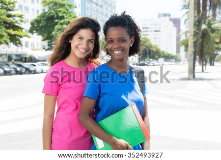 African american student and caucasian student in city - stock photo