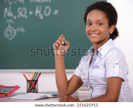 African American student doing math problems on the chalkboard - stock photo