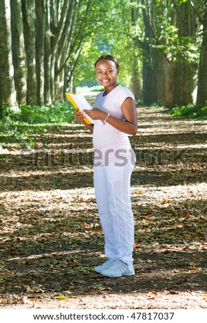 african american student reading book in forest - stock photo