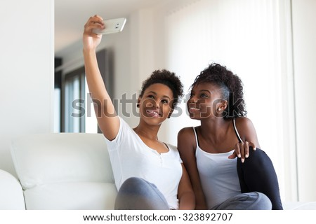 African American teenage girls taking a selfie picture with a smartphone - stock photo