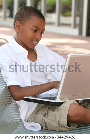 African American Teenager Boy on Laptop Computer Outdoors on a bench, city street, urban setting - stock photo