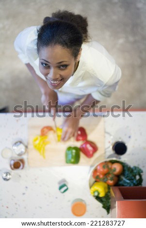 African American woman chopping vegetables - stock photo