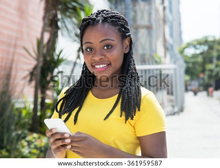 African american woman in a yellow shirt typing message with mobile phone - stock photo