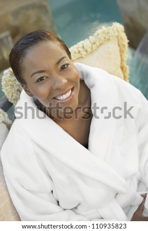 African American woman in bathrobe sitting on a chair - stock photo