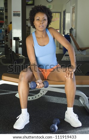 African American woman lifting weights at a gym - stock photo