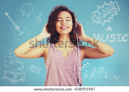 African American woman listening to music in headphones on blue background - stock photo