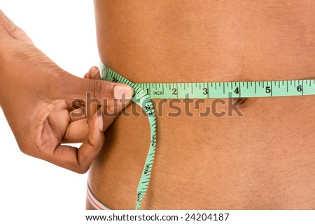 African American woman measures her waist using green measuring tape - stock photo