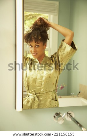 African American woman putting up hair - stock photo