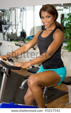African American woman riding an exercise bike - stock photo
