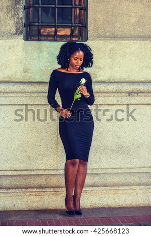 African American Woman seeking love in New York, wearing long sleeve, off shoulder dress, holding white rose, standing against vintage wall on street, looking down, thinking. Instagram filtered effect - stock photo