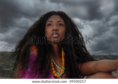 African American woman sits in the safari; staring, and thinking - stock photo