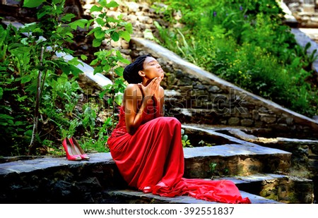 African-American woman sitting on a background of green plants in the rocks in a red dress - stock photo
