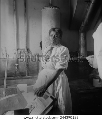 African American woman standing by a washtub with her hand on a washboard. Ca. 1920. - stock photo